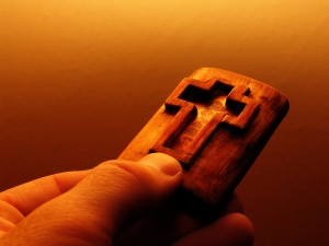 Cross carved in the wood hold by a reaching out hand.